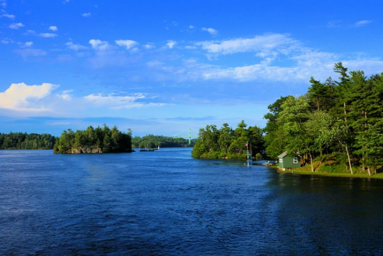 Peaceful landscape of the Thousand Islands during summer with bridge in background along Canada USA border