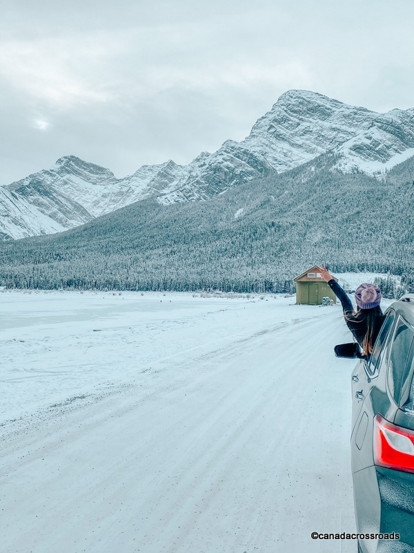 Driving in Canmore in winter, girl in a car with mountains