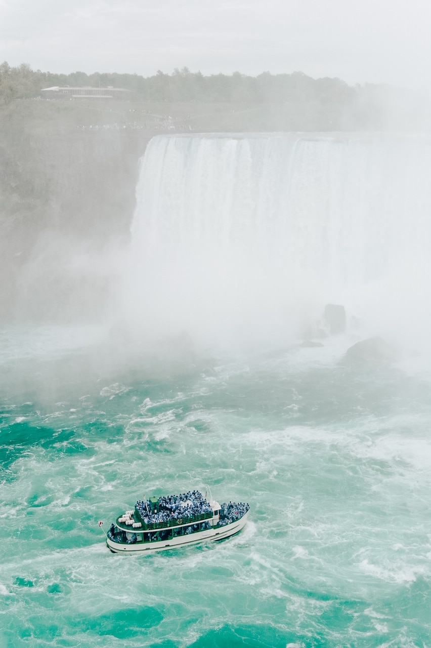 Niagara Falls and boat full of people on the river in mist major Canadian American landmark